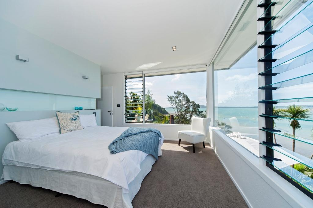 Louvre windows with clear glass blades in the bedroom optimise views and fresh air
