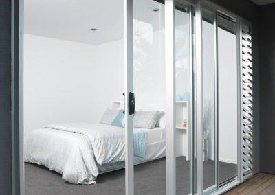 Breezway_louvres_next_to_sliding_doors_in_bedroom