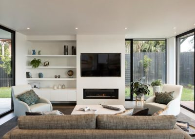 Living room with tall narrow Breezway louvres next to fixed lite glazing. Photo credit Simon Devitt